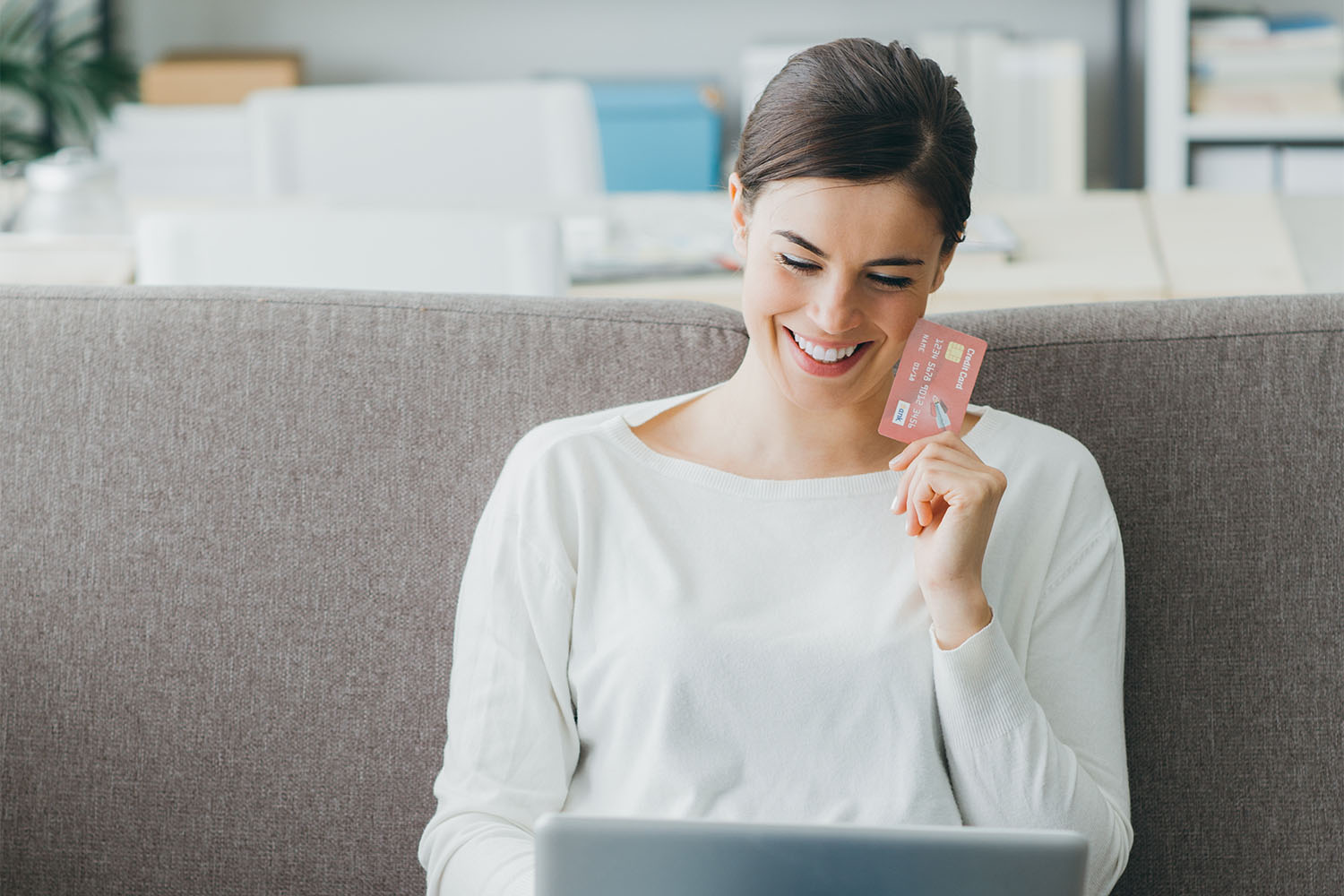 Happy woman on the sofa at home shopping online with a credit card and a laptop